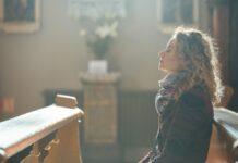 Eine Frau sitzt mit geschlossenen Augen auf einer Kirchenbank.