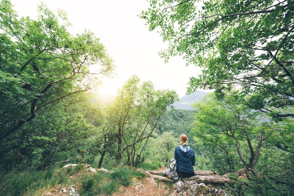 Frau auf einer Baumwurzel im Wald