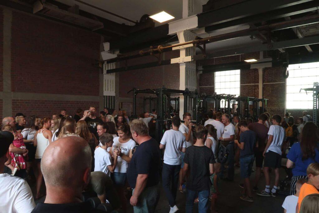 Eine Menschenmenge tummelt sich in dem neuen Kraftraum in der Industriehalle.