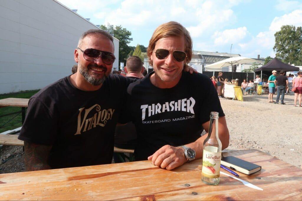gym80-Geschäftsführer Samil Yilmaz links) und Fernseh-Schauspieler Henning Baum rechts) sitzen auf einer Bierzeltgarnitur vor der Industriehalle.