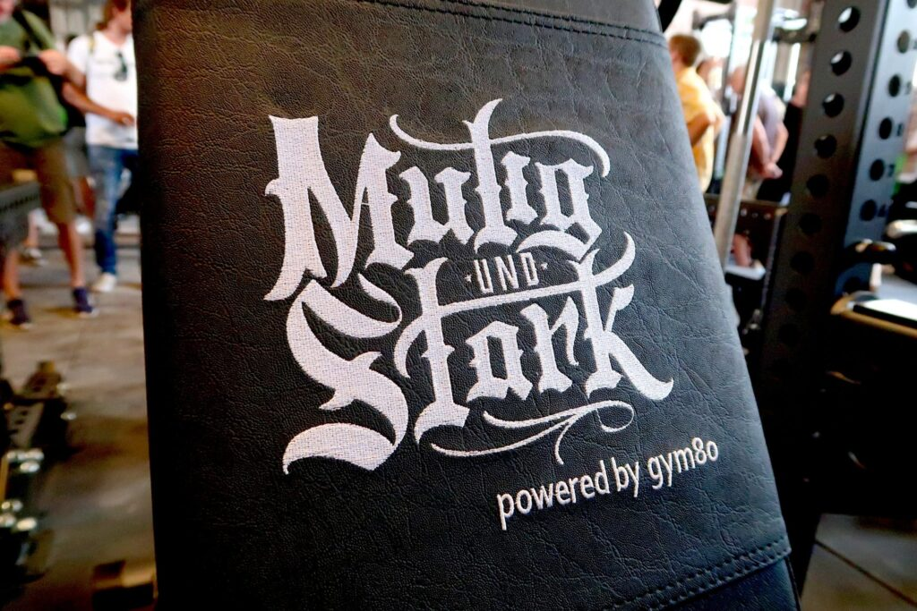 """Eine Hantelbank mit der Aufschrift """"Mutig und Stark - powered by gym80""""."""